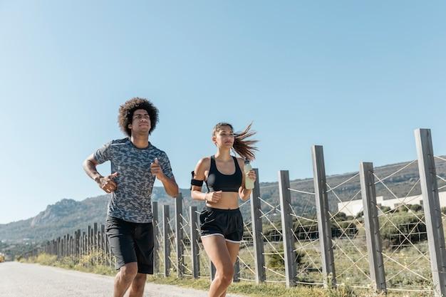 Jovem e mulher correndo na estrada Foto gratuita
