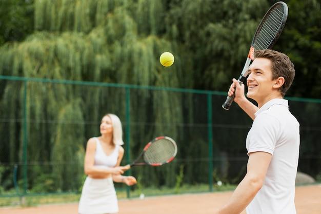 Jovem e mulher jogando tênis Foto gratuita