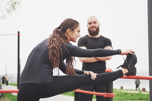 Jovem e mulher realizam exercícios e estrias antes de praticar esportes Foto gratuita