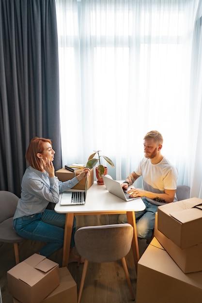 Jovem e mulher sentada à mesa, trabalhando no laptop no escritório de trabalho conjunto Foto gratuita