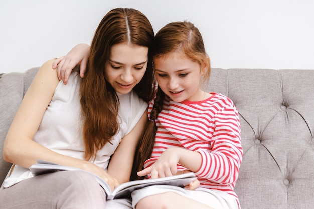 Jovem e sua filhinha filha sentada lendo livros no sofá em casa Foto Premium