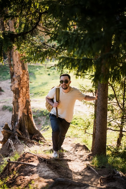 Jovem elegante bonito vestindo camiseta branca e óculos de sol com mochila na mão está viajando na floresta. posando na câmera perto de árvore Foto Premium