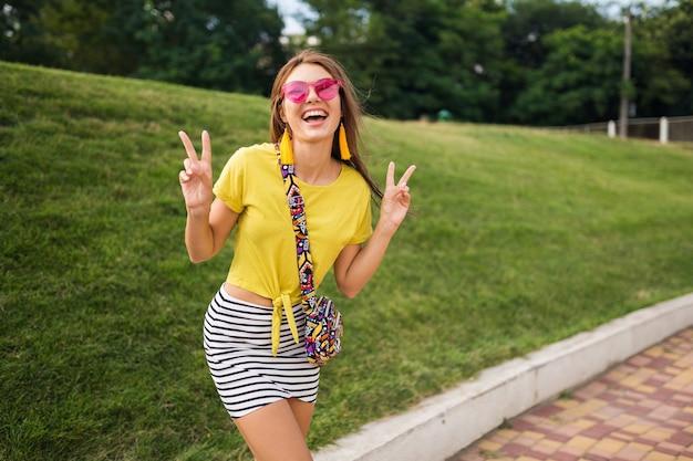 Jovem elegante e sorridente se divertindo no parque da cidade, sorrindo, humor alegre, positiva, emocional, vestindo blusa amarela, minissaia listrada, bolsa, óculos de sol rosa, tendência da moda no estilo de verão Foto gratuita