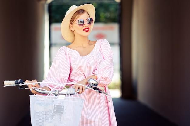 Jovem elegante linda garota sexy em um terno rosa e um chapéu de palha, passeio pela cidade de bicicleta e ri. o conceito de estilo de vida saudável e estilo de vida com estilo Foto Premium