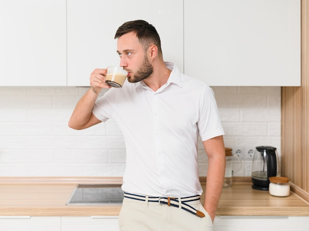Jovem em camiseta tomando um café na cozinha Foto gratuita