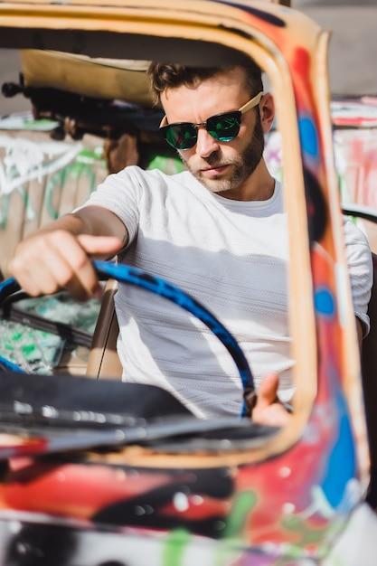 Jovem em óculos de sol em um cabriolet Foto gratuita