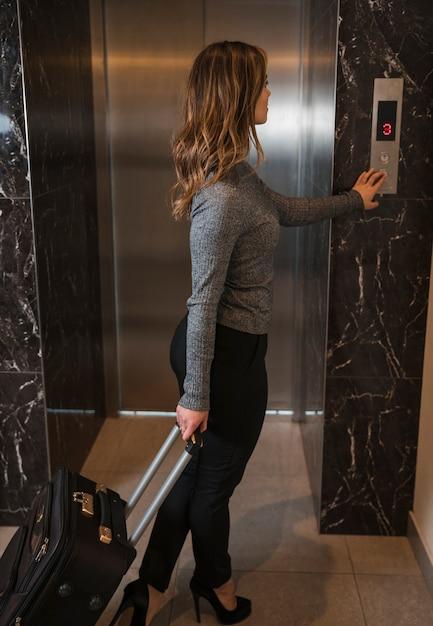Jovem em pé feminino com mala pressionando o botão para um elevador Foto gratuita