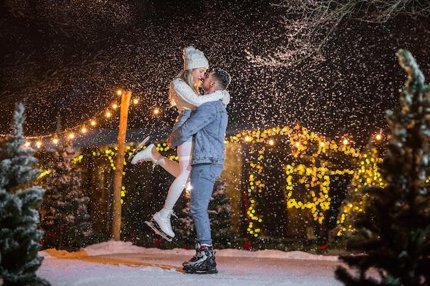 Jovem em roupas jeans, segurando a jovem mulher loira na pista de gelo. Foto Premium