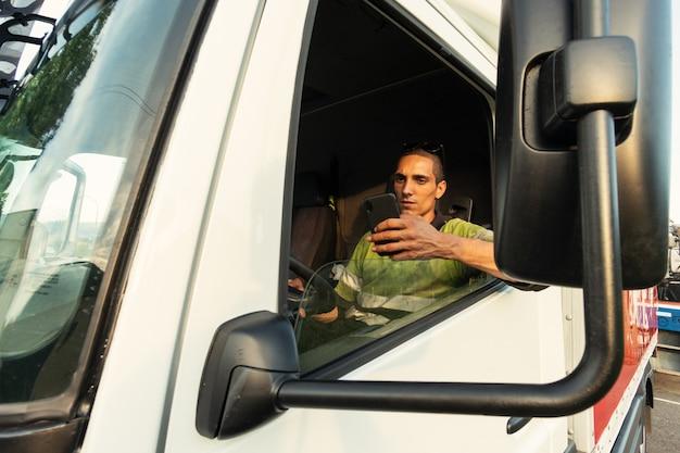 Jovem em seu caminhão dentro da cabine com as roupas de segurança usando o smartphone Foto Premium
