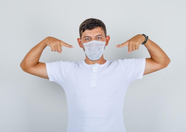 Jovem em t-shirt branca, apontando os dedos para a máscara médica, vista frontal. Foto gratuita