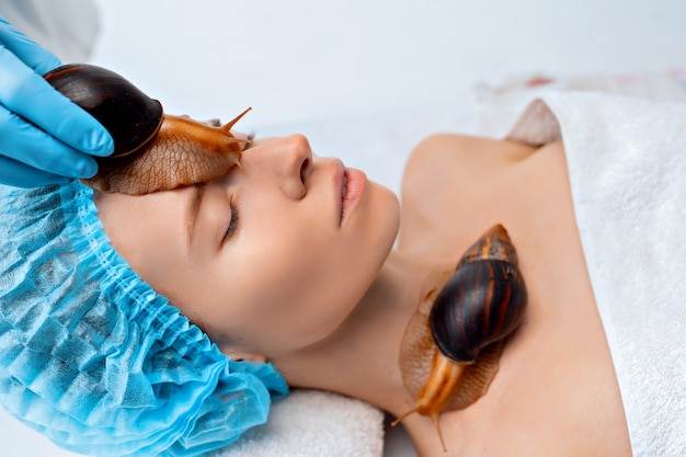 Jovem em tratamento com caracóis gigantes de achatina no salão de beleza Foto Premium