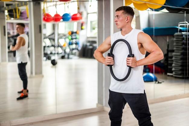 Jovem em treinamento corporal, olhando no espelho Foto gratuita
