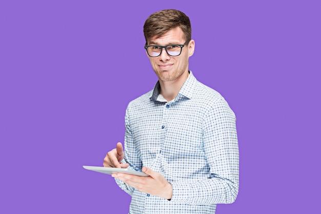 Jovem em uma camisa trabalhando no laptop roxo Foto gratuita