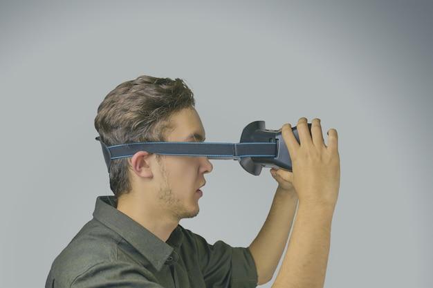 Jovem em uma camisa usa óculos de realidade virtual sobre o fundo cinza claro Foto Premium
