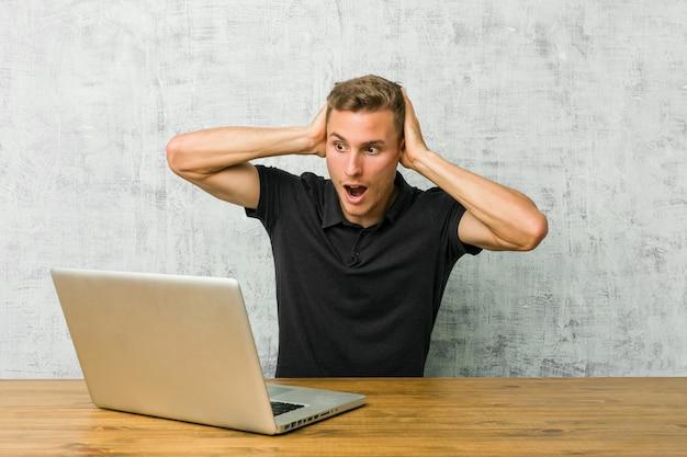 Jovem empreendedor trabalhando com seu laptop em uma mesa cobrindo os ouvidos com as mãos tentando não ouvir som muito alto Foto Premium