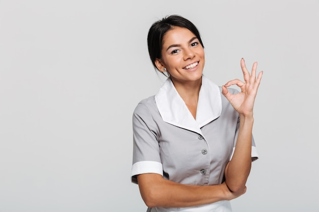 Jovem empregada atraente de uniforme mostrando o gesto ok em pé Foto gratuita