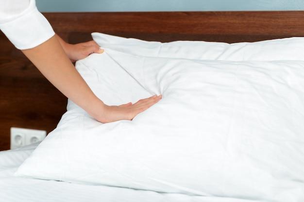 Jovem empregada fazendo cama no quarto de hotel Foto Premium