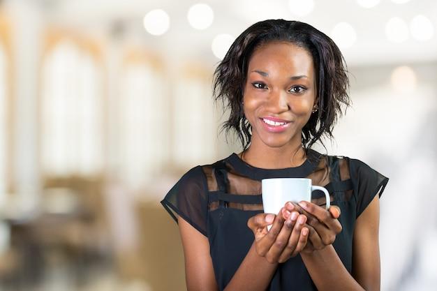 Jovem empresária africana bebendo café enquanto trabalhava no escritório Foto Premium