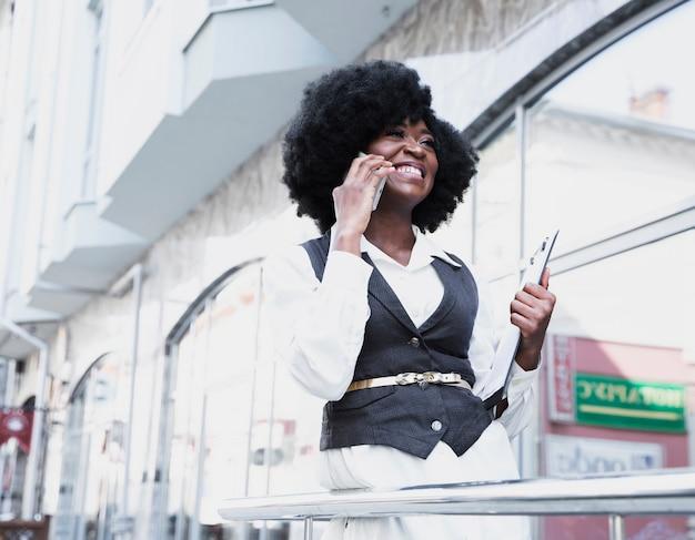 Jovem empresária africana em pé fora do prédio falando no telefone inteligente Foto gratuita