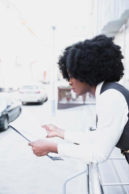 Jovem empresária africana encostado no documento de leitura de trilhos no papel Foto gratuita