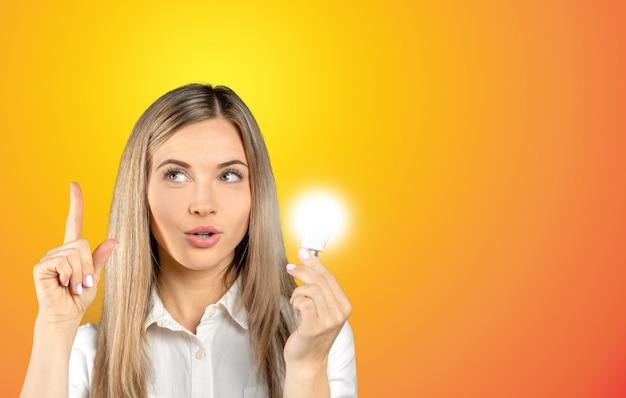 Jovem empresária ao lado do símbolo da lâmpada incandescente Foto Premium