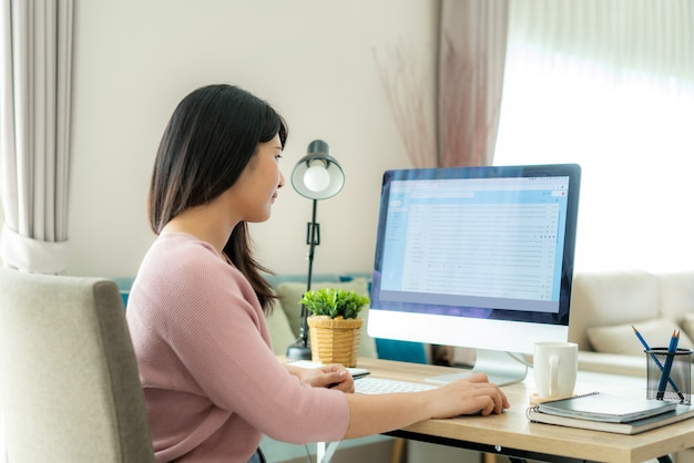Jovem empresária asiática usando o computador, verificando o trabalho de email em casa Foto Premium