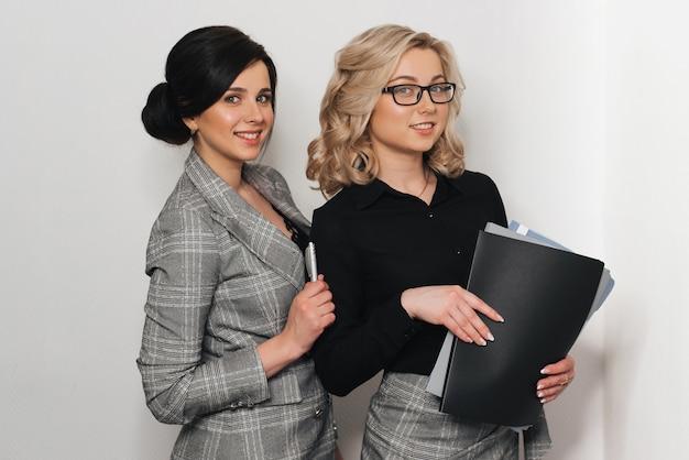 Jovem empresária bem-sucedida em copos com documentos sorrindo Foto Premium