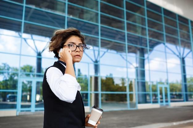 Jovem empresária bem-sucedida, falando no telefone, em pé perto do centro de negócios. Foto gratuita