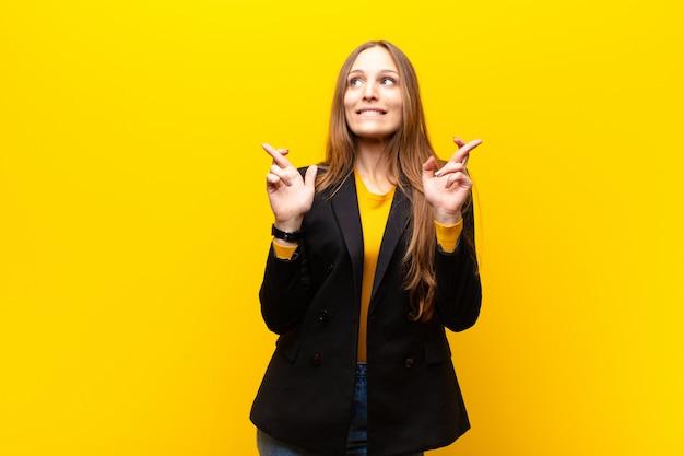 Jovem empresária bonita sorrindo e cruzando ansiosamente os dois dedos, sentindo-se preocupada e desejando ou esperando boa sorte contra o fundo laranja Foto Premium