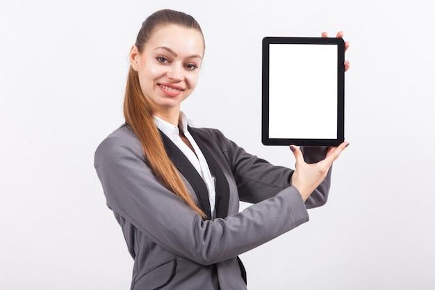 Jovem empresária caucasiana atraente no terno cinza segurar o tablet vazio Foto Premium