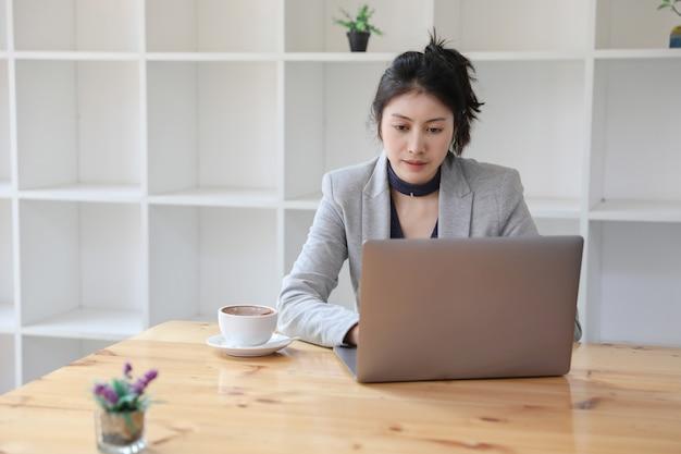 Jovem empresária caucasiana, trabalhando no laptop com café quente na mesa de madeira em confinamento. trabalho a partir de casa. Foto Premium
