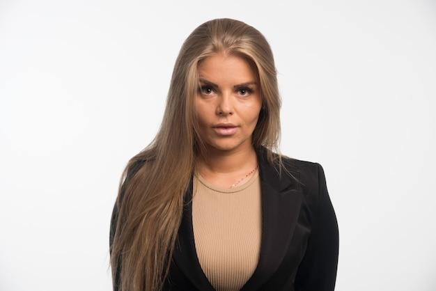Jovem empresária em terno preto posando. Foto gratuita