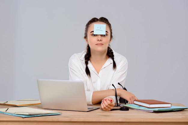 Jovem empresária linda sentada com adesivo na testa no local de trabalho Foto gratuita