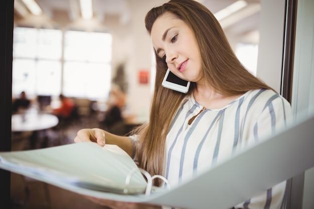 Jovem empresária segurando arquivos enquanto estiver usando o celular na cantina do escritório Foto Premium