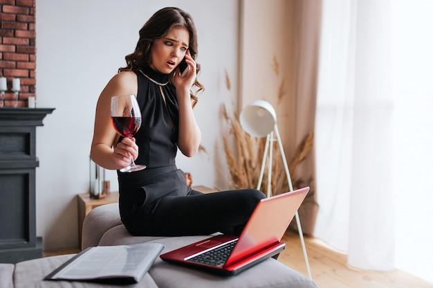 Jovem empresária trabalha em casa. sentado na mesa e falando no telefone. segure o copo de vinho tinto na mão. modelo morena usar vestido preto e xale marrom. Foto Premium