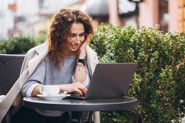 Jovem empresária trabalhando em um computador fora do café Foto gratuita