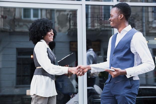 Jovem empresário africano e empresário apertando a mão na frente da janela de vidro Foto gratuita