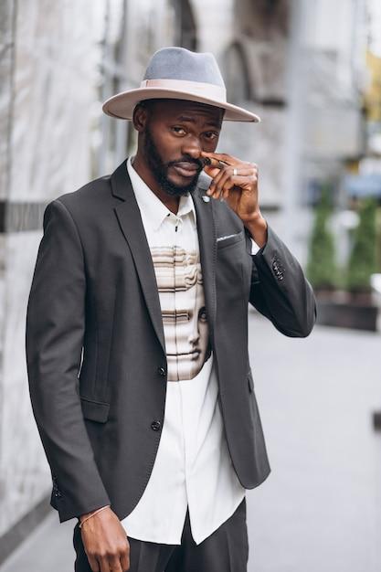 Jovem empresário africano no cigarro de fumo de terno elegante Foto gratuita