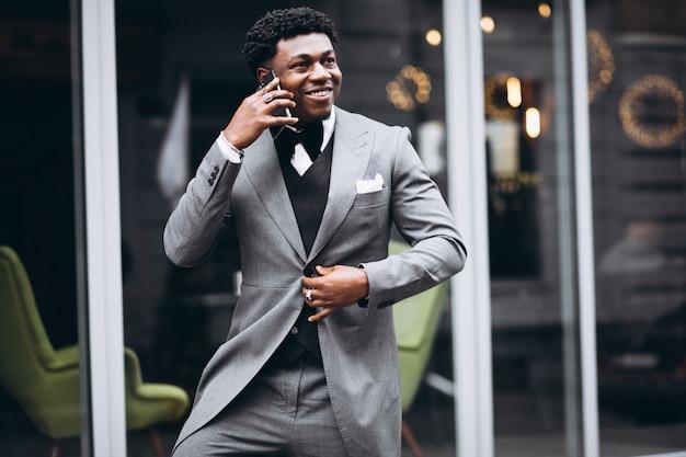 Jovem empresário africano usando telefone Foto gratuita
