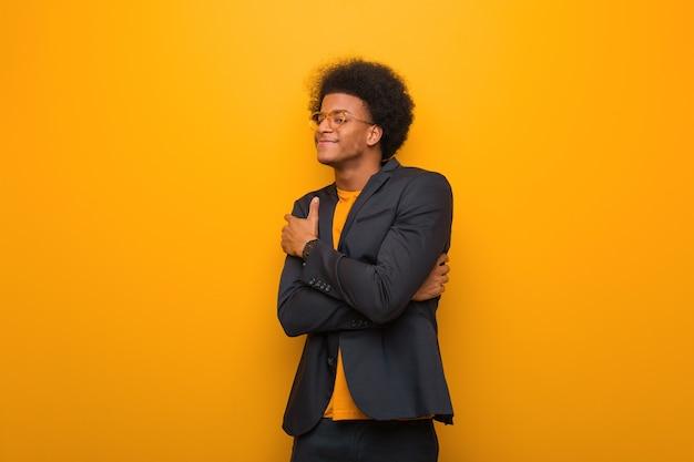Jovem empresário afro-americano numa parede laranja dando um abraço Foto Premium