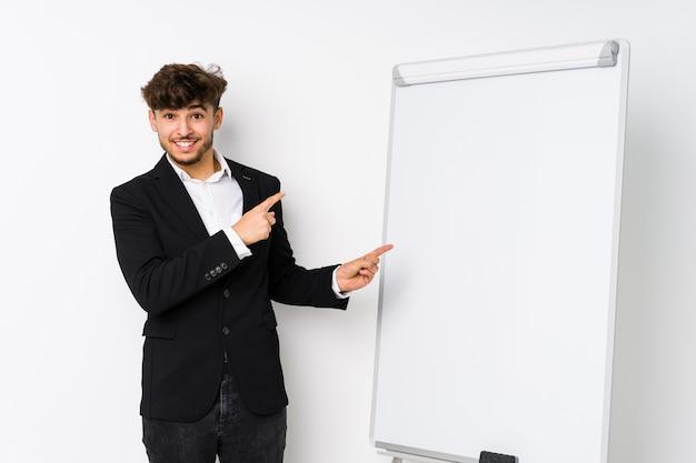 Jovem empresário árabe como treinador chocado, apontando com o dedo indicador para um espaço de cópia. Foto Premium