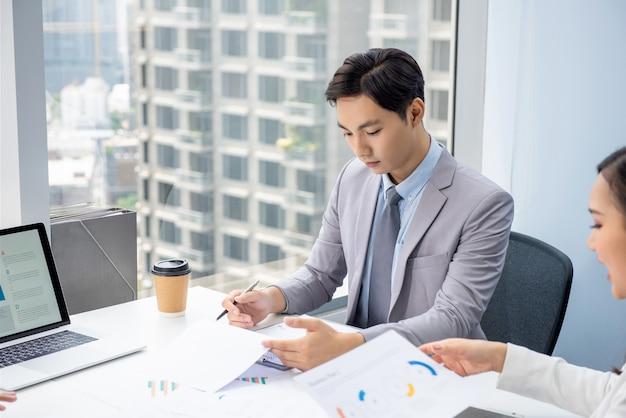 Jovem empresário asiático, concentrando-se na leitura do documento na reunião Foto Premium