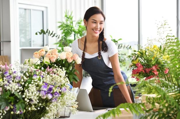 Jovem empresário asiático / dono de loja / florista de um pequeno negócio de loja de flores Foto Premium