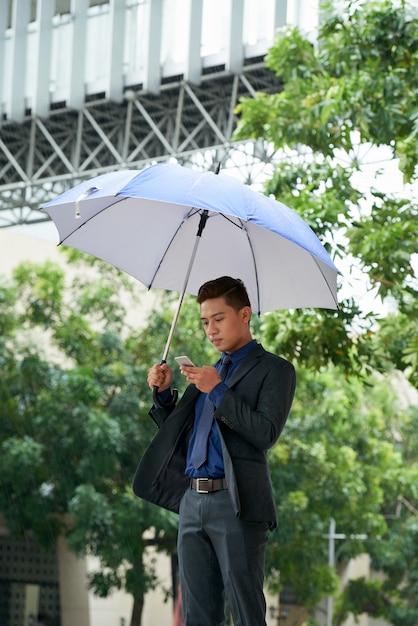 Jovem empresário asiático em pé com guarda-chuva na rua e usando smartphone Foto gratuita