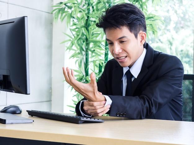 Jovem empresário asiático em terno sentindo dor nas mãos ao usar um notebook no escritório Foto Premium