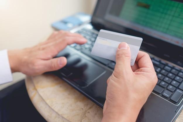 Jovem empresário asiático sentado com laptop e segurando o pagamento com cartão de crédito para compras on-line Foto Premium