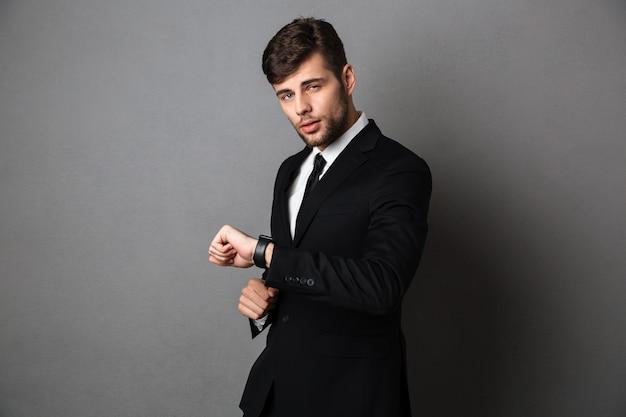 Jovem empresário atraente com roupa formal, verificando o tempo em seu relógio de pulso, Foto gratuita