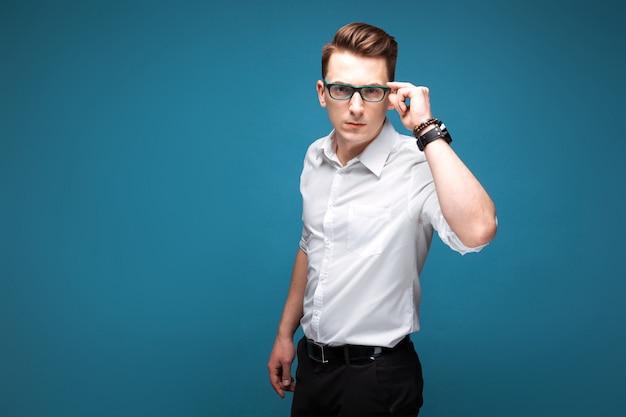 Jovem empresário atraente em relógio caro, óculos escuros e camisa branca Foto Premium