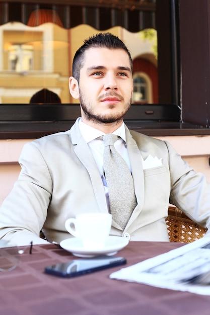 Jovem empresário bebendo uma xícara de café enquanto está sentado em uma mesa de café no terraço Foto Premium