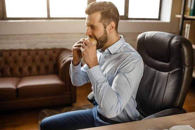 Jovem empresário bonitão come hambúrguer em seu próprio escritório. ele se senta à mesa e morde a refeição. delicioso doentio. pausa. luz do dia. Foto Premium